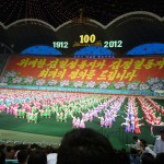 A scene from North Korea's Arirang festival where thousands of people take part in a beautifully choreographed combination of dance, music, gymnastics and drama. The background which changes throughout the performance is a mosaic created by 30,000 students holding flags.