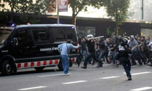 Barcelona, Spain, 29 March 2012: Workers and their supporters attack a police van during a general strike by Spanish workers against reforms making it easier for bosses to slash jobs, wages and conditions.