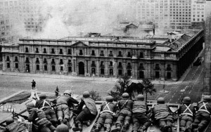 "Chile, 1973: Soldiers attack the presidential residence where President Salvador Allende was residing. A socialist, Allende, popularly elected in 1970, tried to institute pro-working class measures and promised a ""peaceful"", ""constitutional"" road to socialism. The Chilean capitalist state that he administered had other ideas. They overthrew him in the violent 1973 coup. The resulting military dictatorship, led by coup leader General Augusto Pinochet, was responsible for murdering and torturing tens of thousands of leftists."