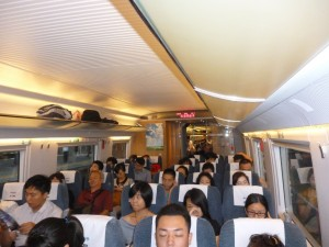 "Passengers aboard the 300 km/h Beijing to Tianjin express train. The continued success of the Chinese workers state in development and pulling people out of poverty is a big blow to Western propaganda that ""Communism is Dead."" Socialists around the world must defend the Chinese workers state from the threat of capitalist counterrevolution. Counterrevolution is threatened by a combination of external, imperialist pressure and internal, pro-capitalist campaigning by the Chinese capitalists spawned by the wavering Chinese rulers' pro-market reforms."
