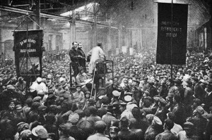 Russia, 1917: Mass political meeting of workers at the giant Putilov factory. This factory which produced railway vehicles as well as artillery and other metal products was a stronghold of the Bolsheviks. Banners and speakers proclaimed the unity of the toilers of all races and peoples.