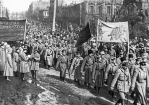 """Red Army troops march triumphantly through Kiev. The partly shown banner on the left of the photo displays a key slogan of the Bolshevik Revolution which translates as """"Proletarians of All Countries Unite."""" Ukrainian and Russian workers must again be organised under the internationalist banner of the 1917 Russian Revolution."""