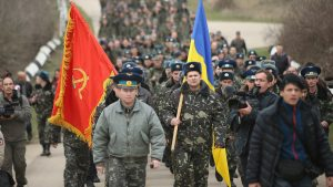 Crimea, March 2014: Ukrainian colonel leads his troops to try and take back the Belbek Airfield from Russian forces. His troops marched both behind the capitalist Ukraine flag and a communist, Soviet Red Army flag. Continued sympathy for the former Soviet Union amongst the masses of the Ukraine and Russia means that even bourgeois, anti-working class forces like the Ukrainian and Russian militaries sometimes use Soviet symbols in order to gain acceptance.