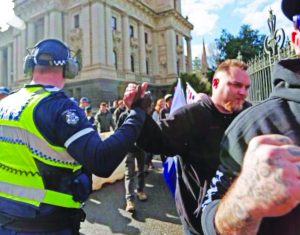 Showing which side they are on! A policeman publicly high-fives a member of the fascist United Patriots Front during their 18 July 2015 race-hate rally in Melbourne. As a core part of the capitalist state, the police in this current system cannot be allies in the anti-fascist struggle but are, instead, a major force impeding the fight against fascism.