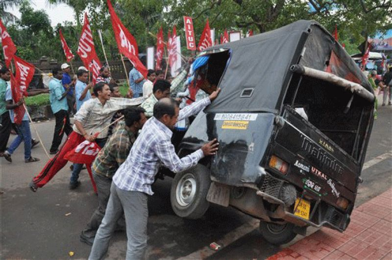 Striking Indian workers pushing over a scab van
